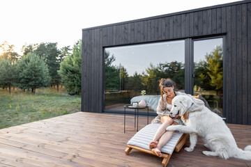 Fototapeta Woman resting on sunbed on wooden terrace near the modern house with panoramic windows near pine forest while playing with pet. Concept of solitude and recreation on nature obraz