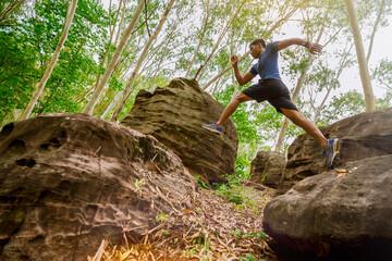 Fototapeta Sport running man in cross country trail run jumping on the rocky mountain path. obraz