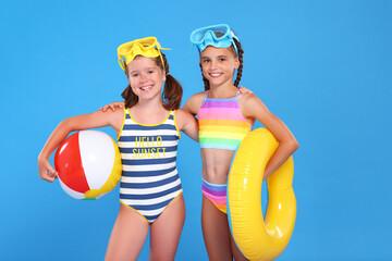 Fototapeta Two little girls in swimwear bathing suits posing isolated on blue studio background obraz