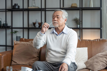 Old senior asian male hand nasal swab testing rapid tests by himself for detection of the SARS co-2...