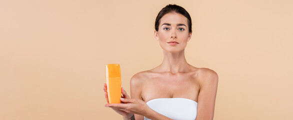 Fototapeta young woman in strapless top showing bottle of sunblock isolated on beige, banner obraz