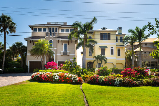 Bonita Springs, Florida gulf of mexico coast with gardens and colorful luxury villa mansion houses buildings modern waterfront architecture and driveway to garage