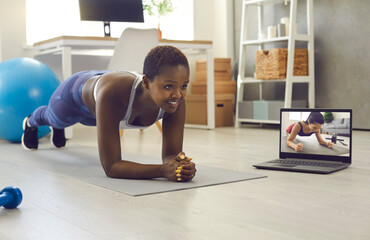 Fototapeta Smiling active sporty athletic young woman practicing sports exercise at home, watching virtual fitness video class with athlete or trainer on notebook PC and doing plank pose good for stomach muscle obraz