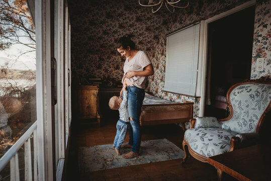 Toddler touching mom's belly in vintage room with wallpaper