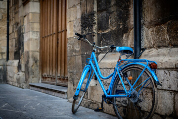 blue bicycle leaning against the wall of an old church
