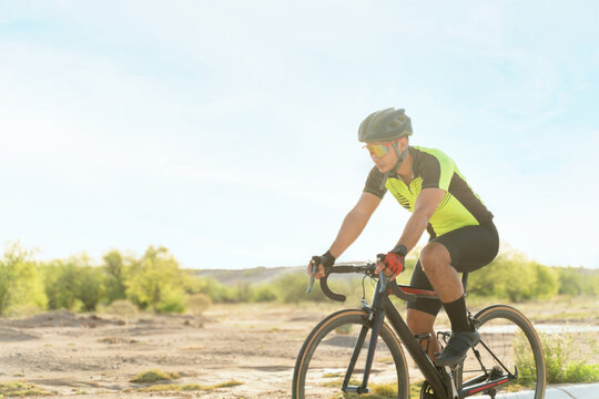 Side view of an athlete riding a bicycle outdoors