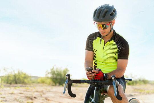 Male cyclist checking his phone after training