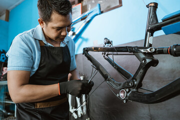 a bicycle mechanic attaches brake cables while assembling a bicycle frame in a repair shop