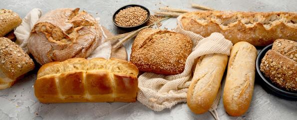 Various types of fresh baked bread on light gray background.