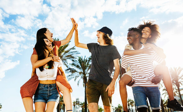 Group of happy multiracial friends celebrating outdoors with back sunlight - Multiethnic people having fun together on holidays while walking in a park- Happiness, friendship and holidays concept
