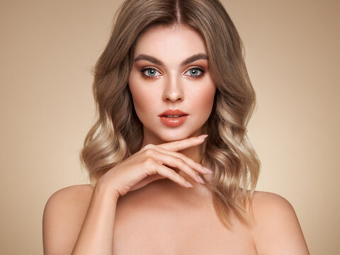 A beautiful young woman with shiny wavy blonde hair. Model with healthy skin, close up portrait. Cosmetology, beauty and spa