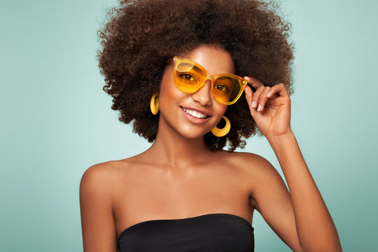Beauty portrait of African American girl in colored sunglasses. Beautiful black woman. Cosmetics, makeup and fashion