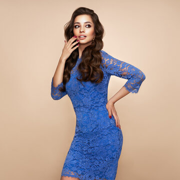 Brunette girl with perfect makeup. Smiling beautiful model woman with long curly hairstyle. Care and beauty hair products. Model in evening blue dress