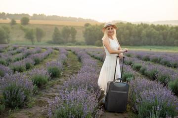 Fototapeta woman with luggage in lavender field obraz