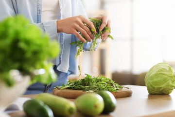 Young woman cooking fresh salad in kitchen