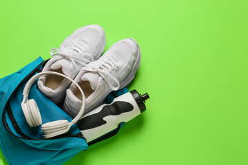 Fototapeta Backpack with sport shoes, bottle of water and headphones on color background obraz