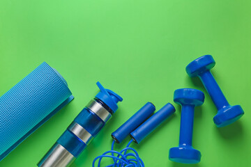 Fototapeta Yoga mat, bottle of water, dumbbells and skipping rope on color background obraz