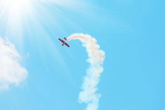 stunt plane trailing smoke bright sun and clouds.