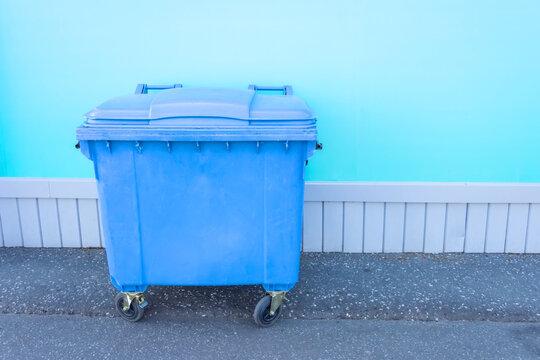Single blue plastic trash can on wheels near building wall on asphalt.