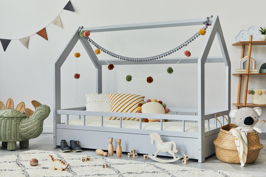 Stylish scandinavian child's room with creative wooden bed, pillows, wooden shelf, plush and wooden toys and hanging textile decorations. Grey walls, carpet on the floor. Template.