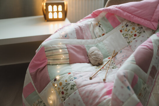 Cozy homely background with wool yarn and knitting needles on an armchair with a blanket.