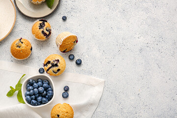Composition with tasty blueberry muffins and berries on light background