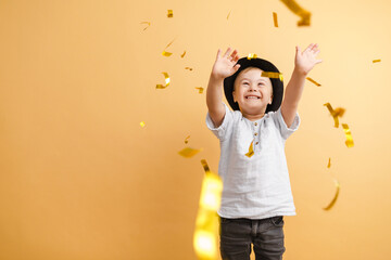 White boy with down syndrome in hat playing with confetti