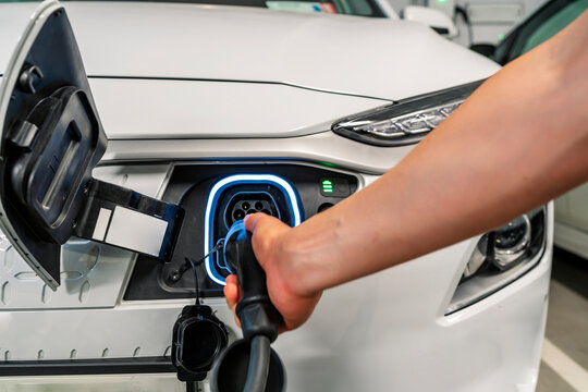 young man charging his non-polluting electric vehicle