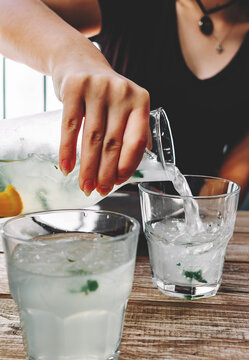 woman hand pouring lemonade or mojito cocktail with lemon, orange and mint with ice on rustic blue background