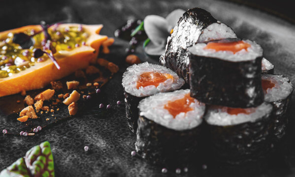 sushi roll in plate on black wooden table background