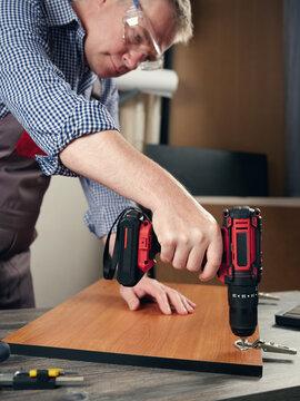 A carpenter makes furniture in a workshop.