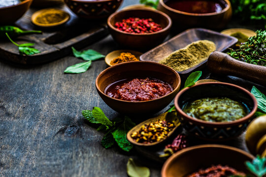 Overhead view of assorted herbs, spices, sauces and seasoning on a table