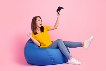 Fototapeta Photo of excited lucky woman dressed yellow t-shirt sitting bean bag holding playstation rising fist isolated pink color background obraz
