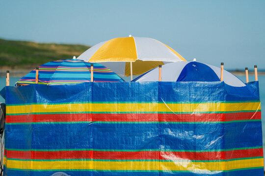 Windbreak and beach umbrellas providing shade, shelter and privacy on a Uk beach.