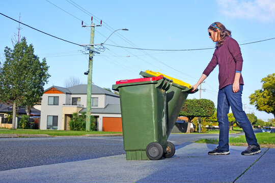 Woman puts recycling bins outside her home on waste collection day