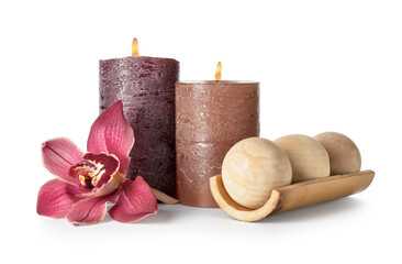 Composition with burning candles, massage balls and orchid flower on white background