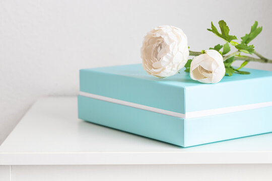 Pastel blue box with peony flower on white table. Gifting and surprise concept.