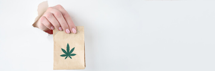 Hand pulling out paper bag of marijuana from torn paper