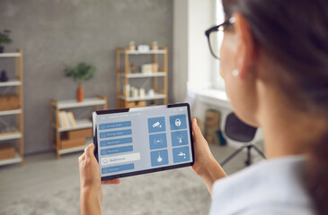 Fototapeta Woman controlling Smart Home with touchscreen tablet. Young lady using mobile interface with wi fi, faucet etc icons to monitor house system. People and technology concept. Close up view over shoulder obraz