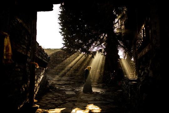 Anonymous woman near stone oriental shrine