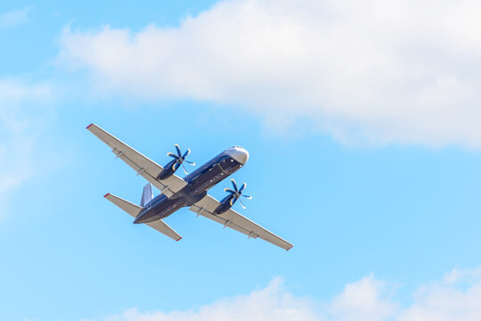An airplane with propellers on its wings flies in the sky.