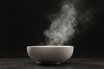 Steaming ceramic bowl on grey table against dark background