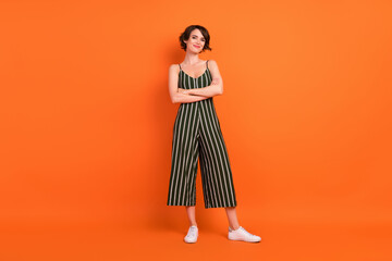 Full length photo of nice brunette millennial lady crossed arms wear overall sneakers isolated on...