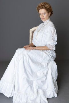 An Edwardian woman wearing a white lace trimmed blouse and skirt