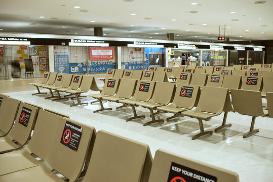 Empty bench seats with social distancing sticker signs during COVID-19 pandemic in Japan 新型コロナウイルス対策で使用禁止のステッカーが貼られたベンチ ソーシャルディスタンス 成田空港