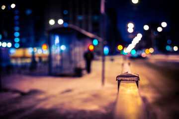 Winter night in the big city, the people waiting at bus stop. Close up view from the handrail on the sidewalk level