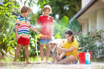 Kids wash dog in summer garden. Water hose fun.