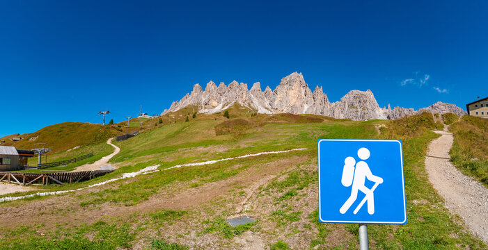 Panoramic view of magical Dolomite peaks of Pizes da Cir, Passo Gardena at blue sky and sunny day with a post sign trailhead showing a walking man, hiker at the tral , South Tyrol, Italy.