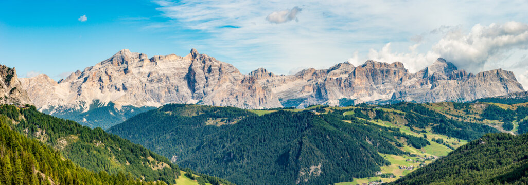 Panoramic view over magical Dolomite granite peaks seen from Passo Gardena, Colfosco, at blue sky and sunny day, South Tyrol, Italy.