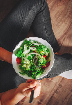 Green vegan breakfast meal in bowl with various fresh mix salad leaves and tomato. Girl in jeans sits on the floor and holding fork with knees and hands visible, top view on wooden background